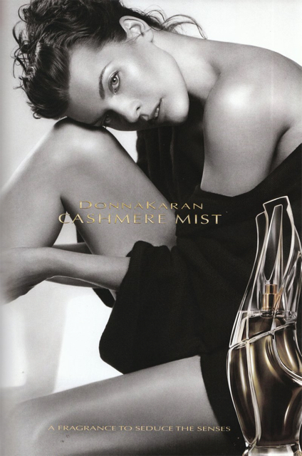 Model with bottle of Donna Karan Cashmere Mist perfume in advertisement