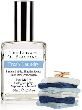 A bottle of Library of Fragrance Fresh Laundry perfume with a stack of laundry